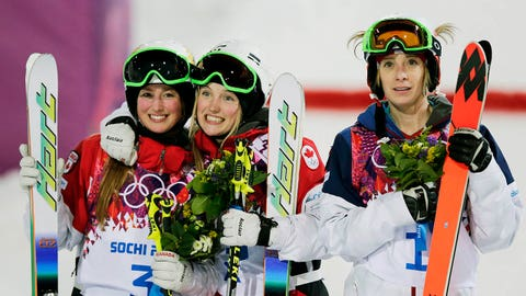 Canada's Justine Dufour-Lapointe, center, celebrates her gold medal in the women's moguls final, with her sister and silver medalist Chloe Dufour-Lapointe, left, and bronze medalist United States' Hannah Kearney, at the Rosa Khutor Extreme Park, at the 2014 Winter Olympics, Saturday, Feb. 8, 2014, in Krasnaya Polyana, Russia.  (AP Photo/Andy Wong)
