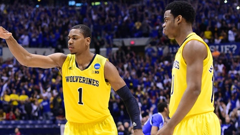 Mar 30, 2014; Indianapolis, IN, USA; Michigan Wolverines forward Glenn Robinson III (1) and guard Derrick Walton Jr. (10) react after time expires in the second half of the finals of the midwest regional of the 2014 NCAA Mens Basketball Championship tournament against the Kentucky Wildcats at Lucas Oil Stadium. Mandatory Credit: Bob Donnan-USA TODAY Sports