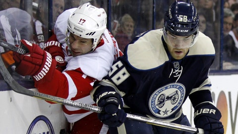 Detroit Red Wings' David Legwand, left, and Columbus Blue Jackets' David Savard work for the puck in the first period of an NHL hockey game in Columbus, Ohio, Tuesday, March 25, 2014. (AP Photo/Paul Vernon)