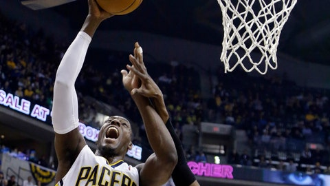 Indiana Pacers center Ian Mahinmi, left, is fouled as he shoots by Utah Jazz guard Alec Burks during the first half of an NBA basketball game in Indianapolis, Sunday, March 2, 2014. (AP Photo/Michael Conroy)