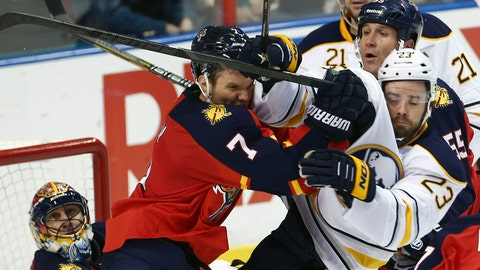 Florida Panthers' Dmitry Kulikov (7) and Buffalo Sabres' Ville Leino (23) collide while chasing the puck during the second period of an NHL hockey game in Sunrise, Fla., Friday, March 7, 2014. (AP Photo/J Pat Carter)