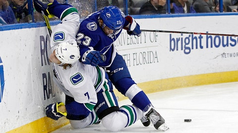 Tampa Bay Lightning right wing J.T. Brown (23) checks Vancouver Canucks left wing David Booth (7) as they battle for the puck during the first period of an NHL hockey game Monday, March 17, 2014, in Tampa, Fla. (AP Photo/Brian Blanco)