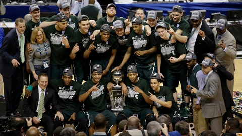 Michigan State players and coaches pose with the championship trophy after they defeated Michigan 69-55 in an NCAA college basketball game in the championship of the Big Ten Conference tournament on Sunday, March 16, 2014, in Indianapolis. (AP Photo/AJ Mast)