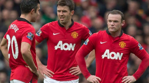 Manchester United's Wayne Rooney, right, Michael Carrick, centre, and Robin van Persie wait for play to restart after Liverpool's first goal during their English Premier League soccer match at Old Trafford Stadium, Manchester, England, Sunday March 16, 2014. Liverpool won the game 3-0. (AP Photo/Jon Super)
