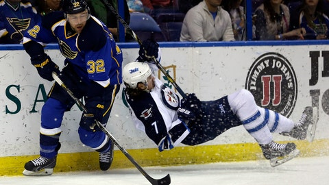 Winnipeg Jets' Keaton Ellerby, right, falls to the ice after being checked into the boards by St. Louis Blues' Chris Porter during the second period of an NHL hockey game Monday, March 17, 2014, in St. Louis. (AP Photo/Jeff Roberson)