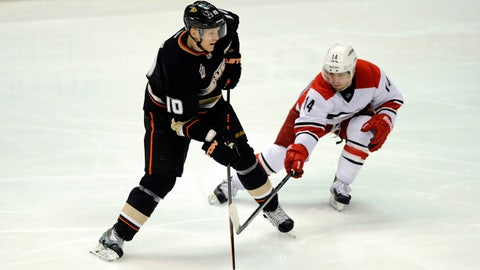 Mar 2, 2014; Anaheim, CA, USA; Anaheim Ducks right wing Corey Perry (10) moves the puck defended by Carolina Hurricanes left wing Nathan Gerbe (14) during the third period at Honda Center. The Anaheim Ducks defeated the Carolina Hurricanes 5-3. Mandatory Credit: Kelvin Kuo-USA TODAY Sports