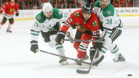 Mar 25, 2014; Chicago, IL, USA; Chicago Blackhawks left wing Brandon Bollig (52) reaches for the puck between Dallas Stars center Vernon Fiddler (38) and left wing Antoine Roussel (21) during the second period at United Center. Mandatory Credit: Jerry Lai-USA TODAY Sports