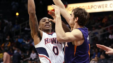 Atlanta Hawks guard Jeff Teague (0) attempts a shot against Phoenix Suns guard Goran Dragic (1) in the first half of an NBA basketball game Monday, March 24, 2014, in Atlanta. (AP Photo/Jason Getz)