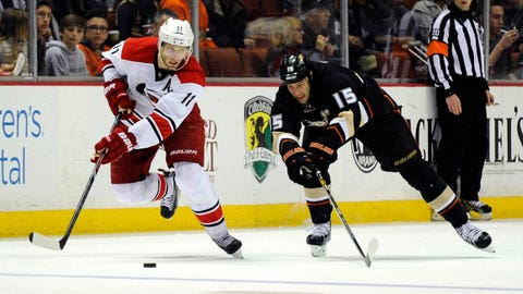 Mar 2, 2014; Anaheim, CA, USA; Carolina Hurricanes center Jordan Staal (11) moves the puck defended by Anaheim Ducks center Ryan Getzlaf (15) during the second period at Honda Center. Mandatory Credit: Kelvin Kuo-USA TODAY Sports