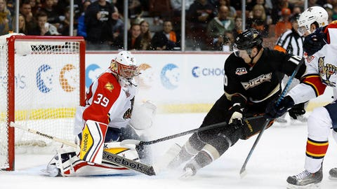 Florida Panthers goalie Dan Ellis makes a save on a shot by Anaheim Ducks right wing Corey Perry, but Perry hit in the rebound for a goal, as Panthers' Tom Gilbert, right, defends during the second period of an NHL hockey game, Sunday, March 23, 2014 in Anaheim, Calif. (AP Photo/Danny Moloshok)