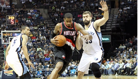Mar 11, 2014; Memphis, TN, USA; Portland Trail Blazers forward LaMarcus Aldridge (12) drives against Memphis Grizzlies center Marc Gasol (33) as guard Courtney Lee (5) looks on during the first quarter at FedExForum. Mandatory Credit: Nelson Chenault-USA TODAY Sports