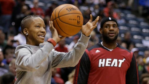 Ebony Nettles-Bey takes a shot during warm-ups, ntext to Miami Heat's LeBron James, before the the Heat's NBA basketball game against the Milwaukee Bucks on Saturday, March 29, 2014, in Milwaukee. (AP Photo/Jeffrey Phelps)