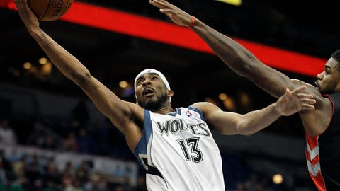 Minnesota Timberwolves forward Corey Brewer (13) goes up to the basket against Toronto Raptors forward Amir Johnson (15) in the second half of an NBA basketball game, Sunday, March 9, 2014, in Minneapolis. The Raptors won 111-104. (AP Photo/Stacy Bengs)