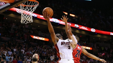 Mar 10, 2014; Miami, FL, USA;  Miami Heat shooting guard Dwyane Wade (3) shoots the ball as Washington Wizards point guard Andre Miller (24) and power forward Drew Gooden (90) defend in the second half at American Airlines Arena. Mandatory Credit: Robert Mayer-USA TODAY Sports