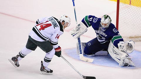 Feb 28, 2014; Vancouver, British Columbia, CAN; Minnesota Wild forward Justin Fontaine (14) scores against Vancouver Canucks goaltender Eddie Lack (31) in a shoot out during sudden death overtime at Rogers Arena. Mandatory Credit: Anne-Marie Sorvin-USA TODAY Sports