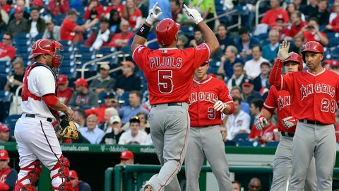 Apr 22, 2014; Washington, DC, USA;  Los Angeles Angels first baseman Albert Pujols (5) celebrates with teammates at home plate after hitting his 499th career home run in the first inning against the Washington Nationals at Nationals Park. Mandatory Credit: Tommy Gilligan-USA TODAY Sports