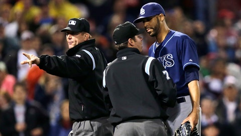 Umpire Jeff Kellogg, left, warns the dugouts as benches clear start to clear after Tampa Bay Rays starting pitcher David Price, right, hit Boston Red Sox's Mike Carp with a pitch during the fourth inning of a baseball game at Fenway Park in Boston, Friday, May 30, 2014. Talking with Price is second base umpire D.J. Reyburn. (AP Photo/Charles Krupa)
