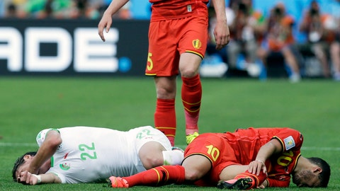 Belgium's Jan Vertonghen looks down as Algeria's Mehdi Mostefa, left, and Belgium's Eden Hazard writhe around on the pitch after a challenge during the group H World Cup soccer match between Belgium and Algeria at the Mineirao Stadium in Belo Horizonte, Brazil, Tuesday, June 17, 2014. (AP Photo/Hassan Ammar)