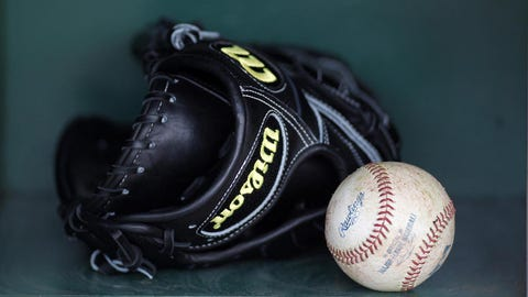 Jun 29, 2013; Pittsburgh, PA, USA; A major league baseball and glove sits in the bat rack in the Pittsburgh Pirates dugout before the game against the Milwaukee Brewers at PNC Park. Mandatory Credit: Charles LeClaire-USA TODAY Sports