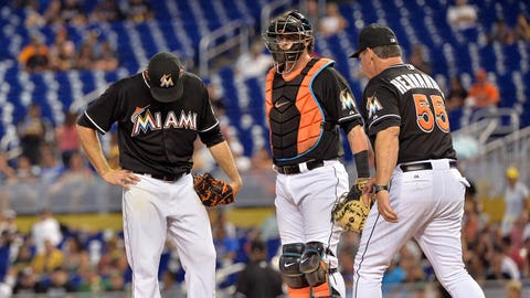 Jun 28, 2014; Miami, FL, USA; Miami Marlins pitching coach Chuck Hernandez (right) walks to the pitchers mound to talk to starting pitcher Nathan Eovaldi (left) as catcher Jarrod Saltalamacchia (center) looks on during the first inning against the Oakland Athletics at Marlins Ballpark. Mandatory Credit: Steve Mitchell-USA TODAY Sports