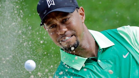 Tiger Woods watches his shot out of a sand trap onto the third green during the first round of the Quicken Loans National PGA golf tournament, Thursday, June 26, 2014, in Bethesda, Md. (AP Photo/Patrick Semansky)