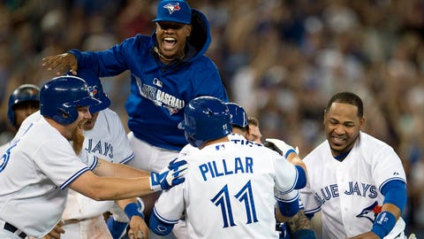 Toronto Blue Jays Jose Kevin Pillar is mobbed by teammates Adam Lind, left, Marcus Stroman, top, and Edwin Encarnacion, right, after hitting the game-winning walk off single during ninth inning of a baseball game against the Minnesota Twins in Toronto on Monday, June 9, 2014. (AP Photo/The Canadian Press, Frank Gunn)