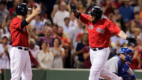 Boston Red Sox pinch-hitter Jonny Gomes is congratulated by teammate Stephen Drew, left, after his two-run home run against the Kansas City Royals during the sixth inning of a baseball game at Fenway Park in Boston, Friday, July 18, 2014. At right is Royals catcher Salvador Perez. (AP Photo/Charles Krupa)