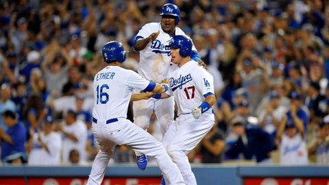 July 12, 2014; Los Angeles, CA, USA; Los Angeles Dodgers third baseman Juan Uribe (5) and center fielder Andre Ethier (16) congratulate catcher A.J. Ellis (17) after he hits a sacrifice RBI in the ninth inning against the San Diego Padres at Dodger Stadium. Mandatory Credit: Gary A. Vasquez-USA TODAY Sports