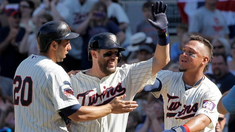 Minnesota Twins' Chris Colabello, left, and Oswaldo Arcia, right, celebrate with Trevor Plouffe, center, after Plouffe grounded into a fielder's choice and Josh Willingham scored the winning run on a throwing error by New York Yankees catcher Francisco Cervelli during the eleventh inning of a baseball game in Minneapolis, Saturday, July 5, 2014. The Twins beat the Yankees 2-1 in 11 innings. (AP Photo/Ann Heisenfelt)