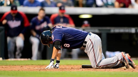 Jul 11, 2014; Denver, CO, USA; Minnesota Twins catcher Kurt Suzuki (8) lays on the ground after he foul tipped off his right leg in the fifth inning against the Colorado Rockies at Coors Field. Mandatory Credit: Ron Chenoy-USA TODAY Sports
