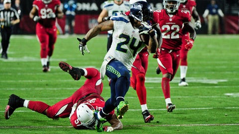 Dec 21, 2014; Glendale, AZ, USA; Seattle Seahawks running back Marshawn Lynch (24) breaks a tackle by Arizona Cardinals outside linebacker Alex Okafor (57) during a 79 yard touchdown run in the second half at University of Phoenix Stadium. Mandatory Credit: Matt Kartozian-USA TODAY Sports