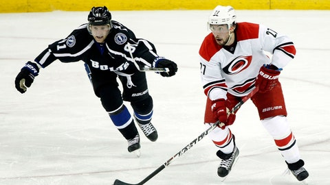 Dec 27, 2014; Tampa, FL, USA; Carolina Hurricanes defenseman Justin Faulk (27) skates with the puck as Tampa Bay Lightning center Steven Stamkos (91) defends during the second period at Amalie Arena. Mandatory Credit: Kim Klement-USA TODAY Sports