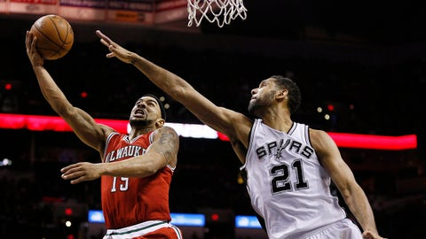 Jan 25, 2015; San Antonio, TX, USA; Milwaukee Bucks point guard Jerryd Bayless (19) shoots the ball past San Antonio Spurs power forward Tim Duncan (21) during the second half at AT&T Center. The Spurs won 101-95. Mandatory Credit: Soobum Im-USA TODAY Sports
