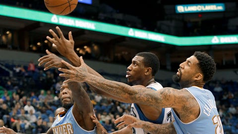 Minnesota Timberwolves forward Thaddeus Young, center,  battles Denver Nuggets guard Nate Robinson, left, and forward Wilson Chandler for a loose ball during the fourth quarter of an NBA basketball game in Minneapolis, Monday, Jan. 5, 2015. The Nuggets won 110-101. (AP Photo/Ann Heisenfelt)