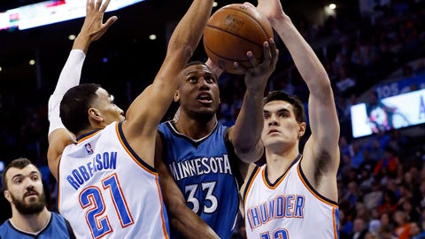 Minnesota Timberwolves forward Thaddeus Young (33) shoots between Oklahoma City Thunder guard Andre Roberson (21) and center Steven Adams, right, in the first quarter of an NBA basketball game in Oklahoma City, Monday, Jan. 26, 2015. (AP Photo/Sue Ogrocki)