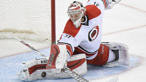Carolina Hurricanes goaltender Anton Khudobin deflects the puck during the second period of an NHL hockey game against the New Jersey Devils on Saturday, Feb. 21, 2015, in Newark, N.J. (AP Photo/Bill Kostroun)