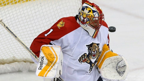 The puck sails close by Florida Panthers goalie Roberto Luongo  as it goes wide in the first period of an NHL hockey game against the Minnesota Wild, Thursday, Feb. 12, 2015, in St. Paul, Minn. (AP Photo/Jim Mone)