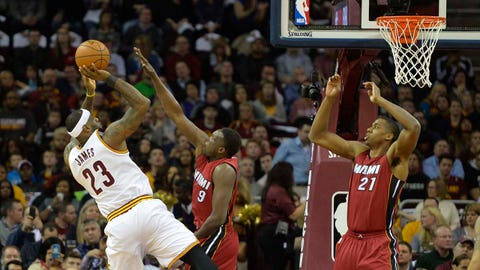 Feb 11, 2015; Cleveland, OH, USA; Cleveland Cavaliers forward LeBron James (23) shoots again Miami Heat forward Luol Deng (9) and center Hassan Whiteside (21) in the first quarter at Quicken Loans Arena. Mandatory Credit: David Richard-USA TODAY Sports