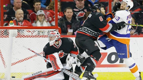 Carolina Hurricanes goalie Anton Khudobin (31) watches a goal scored by New York Islanders' Brock Nelson, not shown, as Hurricanes Tim Gleason (6) and Islanders' Colin McDonald (13) tussle during the second period of an NHL hockey game in Raleigh, N.C., Tuesday, Feb. 17, 2015. (AP Photo/Gerry Broome)