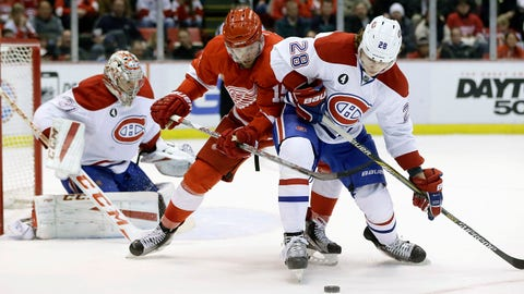 Detroit Red Wings center Riley Sheahan and Montreal Canadiens defenseman Nathan Beaulieu (28) reach for the puck during the second period of an NHL hockey game Monday, Feb. 16, 2015, in Detroit. (AP Photo/Carlos Osorio)