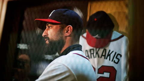 Atlanta Braves newest outfielder Nick Markakis, seen through a locker screen, speaks with reporters in the baseball team's clubhouse, Friday, Dec. 5, 2014, in Atlanta. Markakis signed a four-year contract with the team on Wednesday. (AP Photo/David Goldman)