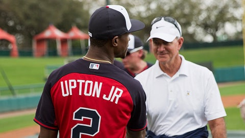 Atlanta Braves' Melvin Upton Jr. wears a jersey with his new name after having it changed on the Braves' roster from B.J. Upton to Melvin Upton Jr., while greeting John Hart, president of baseball operations, during a spring training baseball workout, Monday, Feb. 23, 2015, in Kissimmee, Fla. (AP Photo/David Goldman)