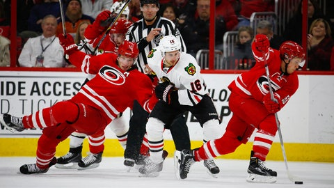 Mar 23, 2015; Raleigh, NC, USA; Carolina Hurricanes forward Jordan Staal (11) is knocked to the ice by Chicago Blackhawks forward Marcus Kruger (16) during the 3rd period at PNC Arena. The Chicago Blackhawks defeated the Carolina Hurricanes 3-1. Mandatory Credit: James Guillory-USA TODAY Sports