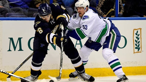 Mar 30, 2015; St. Louis, MO, USA; St. Louis Blues defenseman Zbynek Michalek (6) clears the puck while being pressured by Vancouver Canucks center Henrik Sedin (33) during the first period at Scottrade Center. Mandatory Credit: Jasen Vinlove-USA TODAY Sports