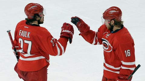 Carolina Hurricanes' Justin Faulk (27) and Elias Lindholm (16), of Sweden, celebrate Faulk's goal against the of the New Jersey Devils during the third period of an NHL hockey game in Raleigh, N.C., Saturday, March 28, 2015. Carolina won 3-1. (AP Photo/Gerry Broome)