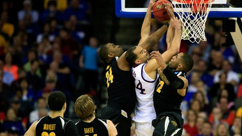 OMAHA, NE - MARCH 22: Perry Ellis #34 of the Kansas Jayhawks has a shot blocked by Shaquille Morris #24 and teammate Tekele Cotton #32 of the Wichita State Shockers in the second half during the third round of the 2015 NCAA Men's Basketball Tournament at the CenturyLink Center on March 22, 2015 in Omaha, Nebraska.  (Photo by Jamie Squire/Getty Images)