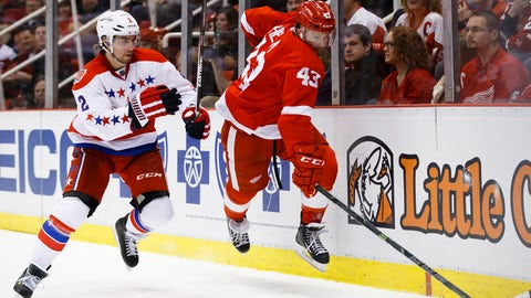 Apr 5, 2015; Detroit, MI, USA; Detroit Red Wings center Darren Helm (43) leaps over Washington Capitals defenseman Matt Niskanen (2) to get to the puck in the third period at Joe Louis Arena. Washington won 2-1. Mandatory Credit: Rick Osentoski-USA TODAY Sports