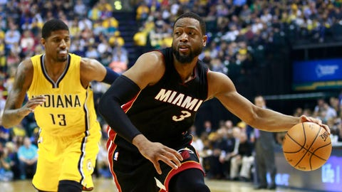 Miami Heat guard Dwyane Wade (3) dribbles the ball as Indiana Pacers forward Paul George defends in the first half of an NBA basketball game Sunday, April 5, 2015, in Indianapolis. (AP Photo/R Brent Smith)