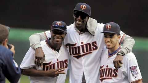 Minnesota Twins' Torii Hunter, Minnesota Timberwolves' Kevin Garnett, center and Duke's Tyus Jones, right, pose for a photo after Garnett throw out the first pitch prior to the Twins' home opener against the Kansas City Royals baseball game, Monday, April 13, 2015 in Minneapolis. Jones delivered the baseball for Garnett's first pitch.(AP Photo/Tom Olmscheid)