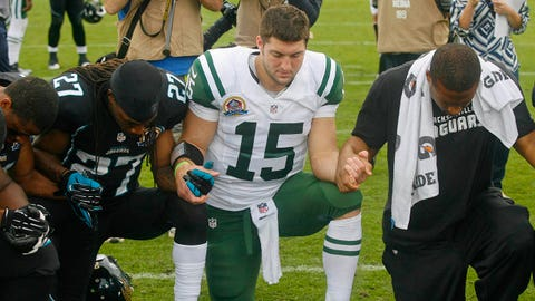 Dec 9, 2012; Jacksonville FL, USA; Jacksonville Jaguars cornerback Rashean Mathis (27) and New York Jets quarterback Tim Tebow (15) join hands in prayer after their game at EverBank Field. The New York Jets beat the Jacksonville Jaguars 17-10. Mandatory Credit: Phil Sears-USA TODAY Sports